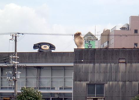 ビルの屋上に置かれた「黒電話」と「右手」のオブジェ